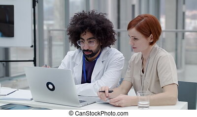 Doctors with laptop sitting and talking at desk, corona ...
