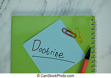 Doctrine write on sticky note isolated on Wooden Table.
