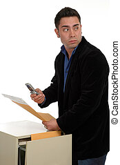 Document Theft - A man slipping documents out of a file...