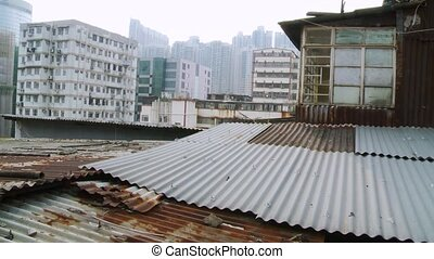 Static camera shooting of a miserable shack made with metal sheets on the rooftop of a Hong Kong building. In the background, typical Asian views.