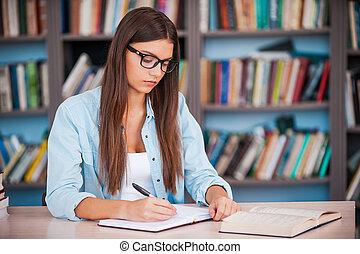 doen, haar, homework., jonge vrouw , schrijvende , iets, in, haar, opmerking blok, en, het boek van de lezing, terwijl, zittende , op, de, bureau, in, de, bibliotheek