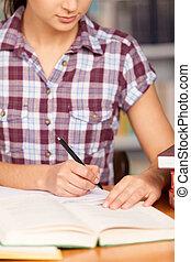doen, haar, homework., jonge vrouw , schrijvende , iets, in, haar, opmerking blok, en, het boek van de lezing, terwijl, zittende , op, de, bureau
