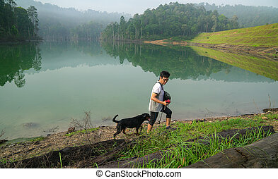 Dog and man hiking in the forest with lake