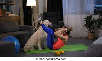 Dog assisting female owner foing crunches at home - Doing...