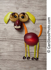 Dog composed with fruits on wooden background