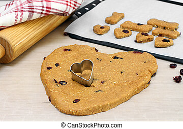 Dog cookie dough made with cranberries, heart shaped with heart cookie cutter. Selective focus on cookie cutter in dough.