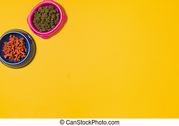 Dog food and accessories on yellow background top view