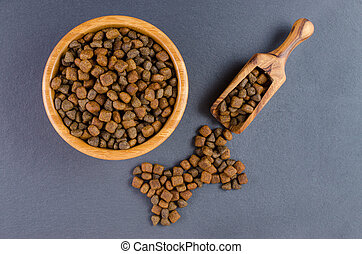 dog food in a bowl and snack like bone on black background, top view
