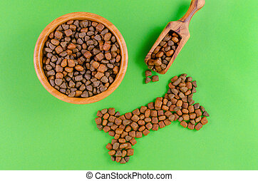 dog food in a bowl and snack like bone on green background, flat lay