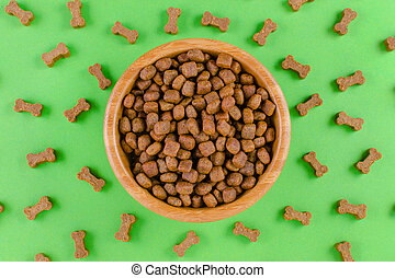 dog food in a bowl and snack like bones on green background, flat lay