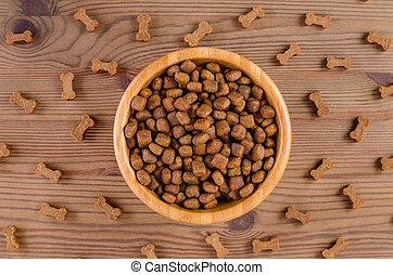 dog food in a bowl and snack like bones on wooden background, flat lay
