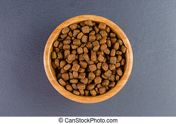 dog food in a bowl on black background, flat lay