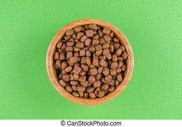 dog food in a bowl on green background, flat lay