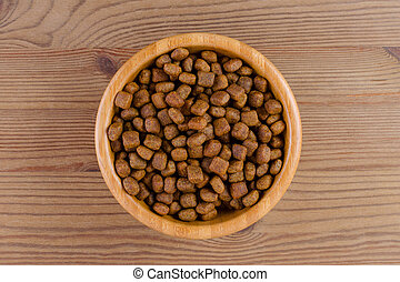 dog food in a bowl on wooden background, flat lay