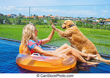 Dog give high five to happy girl swimming in pool