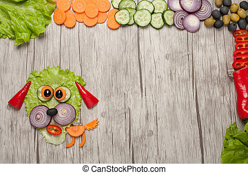 Dog made of fresh vegetables on wooden table