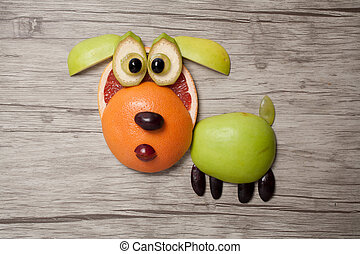 Dog made with fruits on wooden background