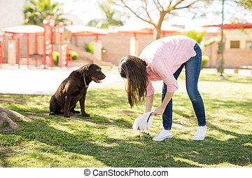 Dog owner picking up after her dog