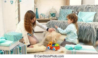 dog playing with children in toys - A girl and a boy scratch...