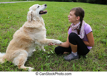 Dog shaking hands with a child
