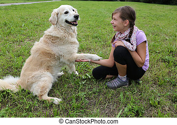 Dog shaking hands with a girl