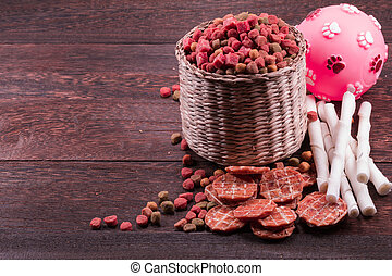 Dog snack ,dog dood, dog chews, dog biscuits,ball toy for dog on a grey wooden table wall background with copy space .