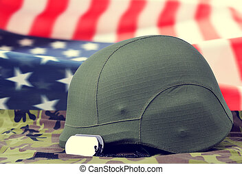 Dog tags and helmet on camouflage fabric in the background American flag.