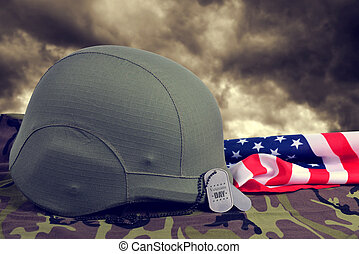 Dog tags,helmet and American flag on camouflage fabric.