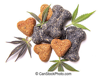 Dog treats and cannabis leaves isolated over white ...