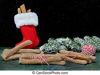 Dog treats being wrapped and put in a red fluffy stocking for Christmas.