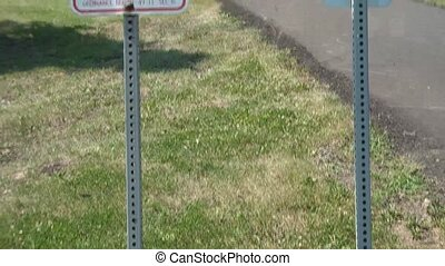 Dog Waste Sign - Fine by City - Panning upward to municipal...