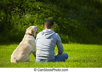 Dog with dog - Young man with his dog on meadow.