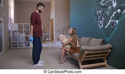 Dog with pet owner meeting vet doctor at clinic