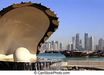The oyster and pearl fountain on the Corniche in central Doha, Qatar, with the Dhow harbour and the new skyline beyond. March 2010