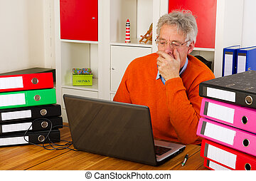 doing administration - Elderly man is sitting with laptop...