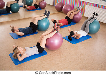 Doing crunches - Young fit people doing crunches with ...