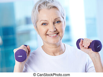 Doing exercise - Portrait of pretty senior woman exercising...