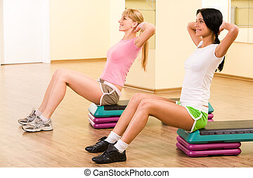 Doing exercise - Two girls sitting in the gymnasium and...