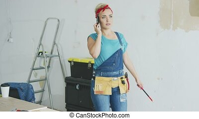 Doing home repairs woman talking on smartphone