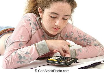 Doing Homework - A teenaged girl studying math, using a...
