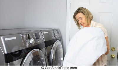Doing Laundry - Mature Woman Loading Bed Sheets Into A...