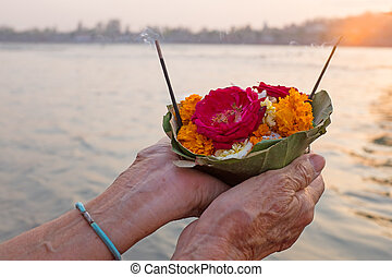 Doing puja at the river Ganges in India at sunset