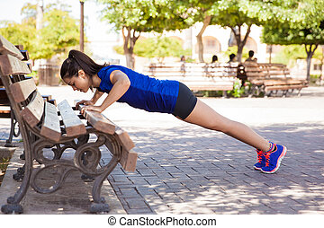Doing push ups at a park - Profile view of a young woman ...