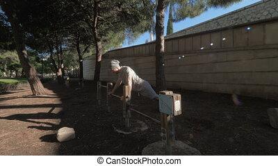 Doing pushups in fresh air - A young man doing pushups in a...