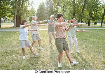 Doing qigong exercise - Group of focused senior people and ...