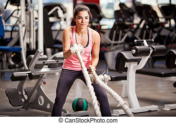 Doing some crossfit exercises - Pretty Hispanic young woman...