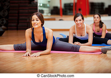 Group of women working on their flexibility and doing some leg splits in a gym