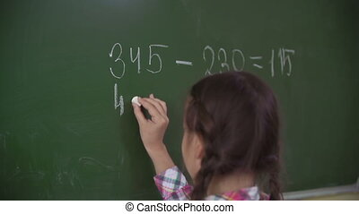 Doing Sums on Chalkboard - School girl doing sums on...