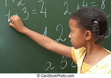Portrait of smart schoolchild standing at blackboard and doing sums