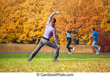 Young woman doing yoga in the autumn park